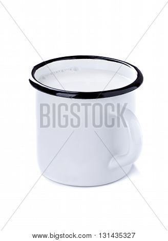 Enamel tin cup with milk isolated on white background.