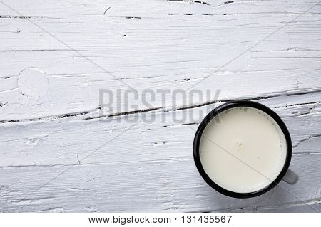 White wooden Board as image background with tin cup of milk textured.
