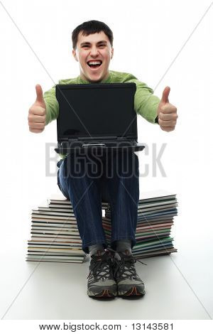 Portrait of a young man sitting on books with a laptop. Theme: education career, success.