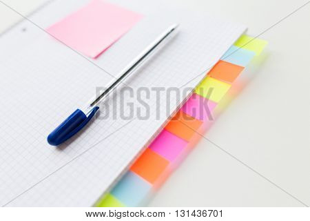 business, information, memo, management and education concept - close up of notebook or organizer with blank tags and pen on office table