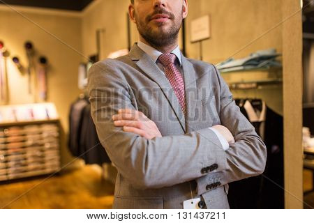 sale, shopping, fashion, style and people concept - close up of man in suit and tie at clothing store