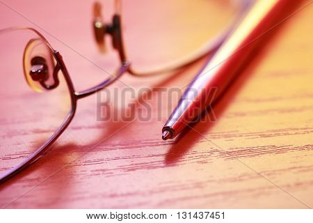 Colorful still life with pen near spectacles on wooden table