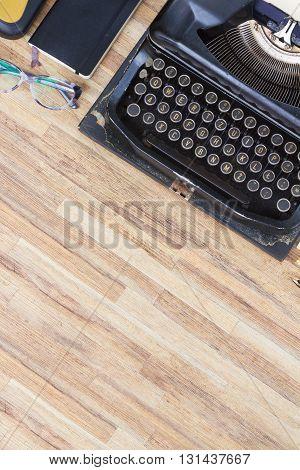black vintage antique typewriter on working wooden desktop with copy space, top view