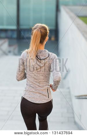 fitness, sport, people and lifestyle concept - close up of sporty woman running downstairs in city