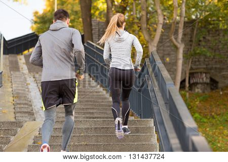 fitness, sport, people and lifestyle concept - couple running upstairs in city park