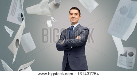 business, people, paperwork, statistics and office concept - happy smiling businessman in dark grey suit over gray background with falling papers