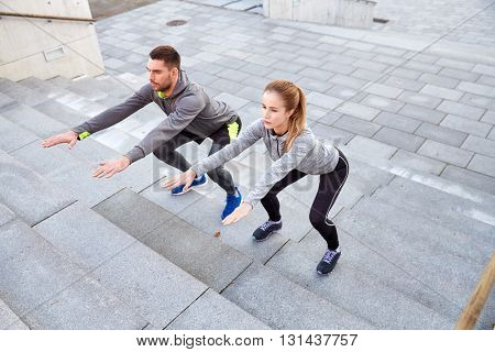 fitness, sport, people, exercising and lifestyle concept - couple doing squats on city street stairs