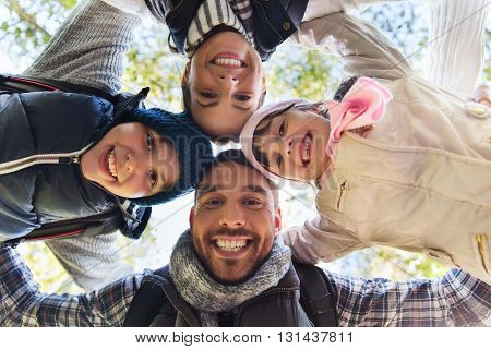 camping, travel, tourism, hike and people concept - happy family faces outdoors at camp in woods