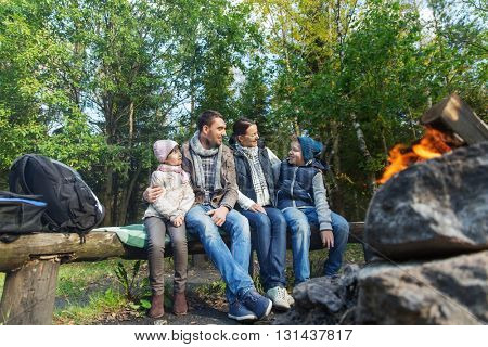 camping, travel, tourism, hike and people concept - happy family sitting on bench and talking at camp near campfire in woods