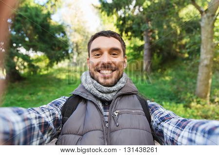 technology, travel, tourism, hike and people concept - happy man with backpack taking selfie and hiking