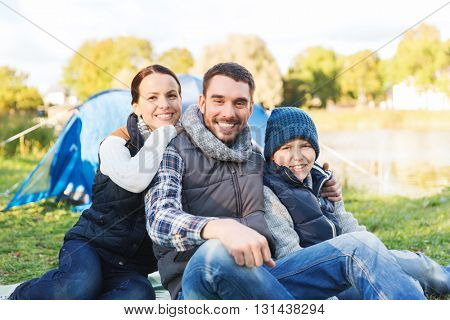 camping, tourism, hike and people concept - happy family over tent at camp site