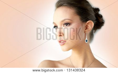 beauty, jewelry, wedding accessories, people and luxury concept - close up of beautiful asian woman or bride with earring over beige background