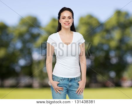 advertisement, clothing and people concept - happy smiling young woman or teenage girl in white t-shirt over summer park background