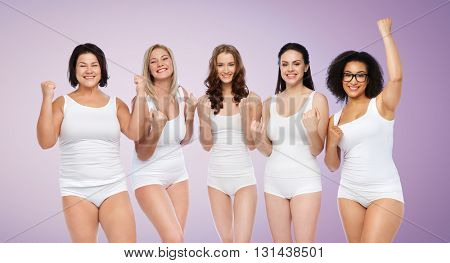 success, friendship, beauty, body positive and people concept - group of happy plus size women in white underwear celebrating victory over violet background