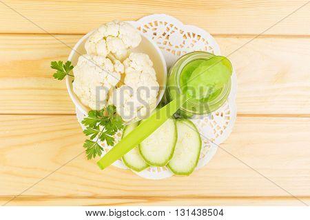 Jar of baby puree of cauliflower, zucchini on a background of light wood.