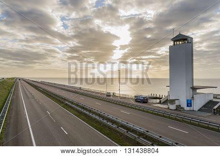 Afsluitdijk The Netherlands - April 19 2016: Afsluitdijk between Friesland and Noord-Holland at the IJsselmeer with highway monument and cars.
