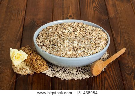 A bowl of oatmeal, bar, rose and spoon on dark wooden background.