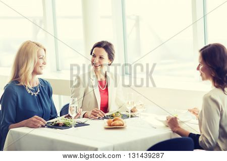 people, holidays, celebration and lifestyle concept - happy women eating and drinking champagne at restaurant