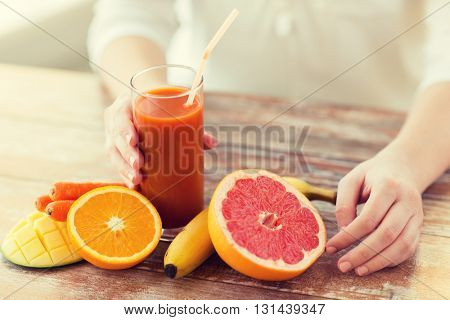 healthy eating, food, dieting and people concept - close up of woman hands with fruits and fresh juice sitting at table