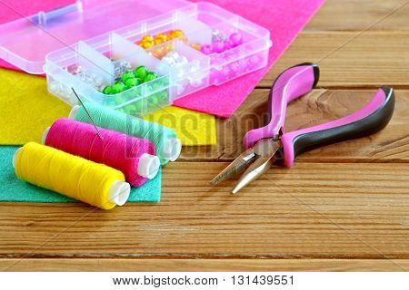 Plastic box with colorful beads, a set of thread, needle, pliers, sheets of felt on wooden background. A set of tools and materials for children's art and crafts
