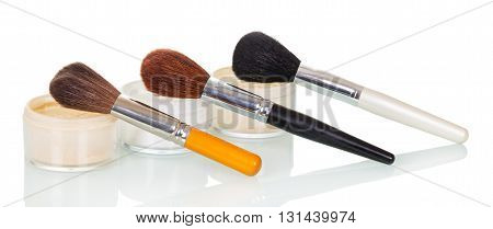 Cosmetic brushes and jars of cream, the foundation isolated on white background.