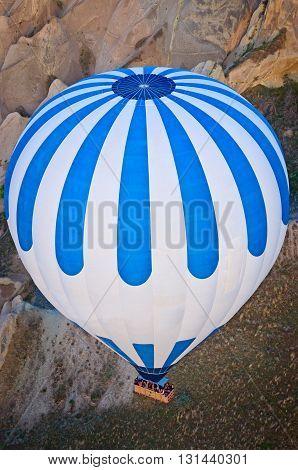 Hot air balloons over mountain landscape in Cappadocia Goreme National Park Turkey.