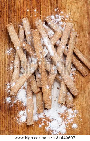 Heap of Freshly Baked Whole Wheat Bread Sticks with Dough closeup on Wooden Cutting Board