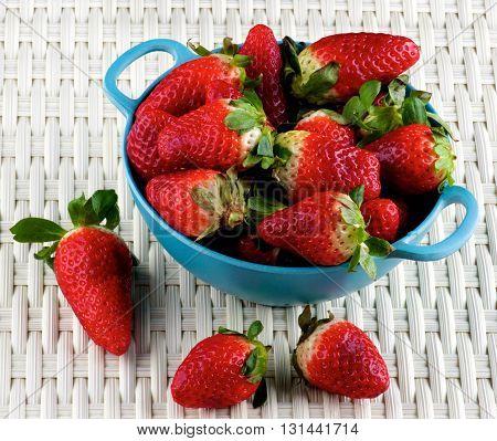 Perfect Big Ripe Strawberries in Blue Colander closeup on Wicker background