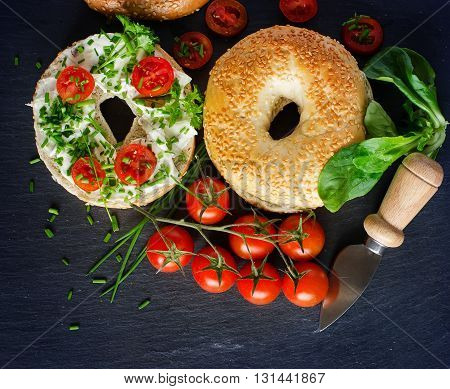 Bagels sandwiches wtih cream cheese tomatoes and chives healthy vegetarian breakfast. Picnic snack.