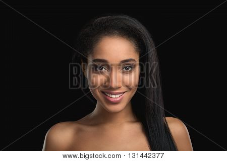 Portrait of smiling handsome nude mulatto woman on dark background. Attractive, satisfied, cheerfull african american girl
