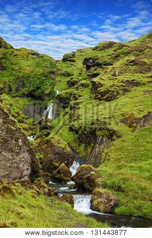 Basalt mountains covered in green moss and grass . Gorgeous cascading waterfall from melting glacier. Iceland, July
