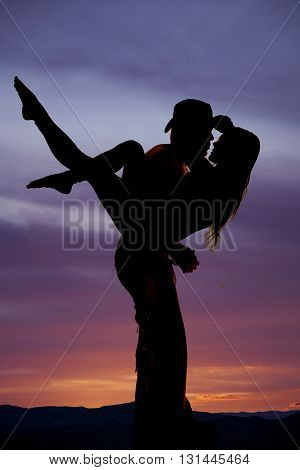 A silhouette of a cowboy holding on to his woman getting ready to kiss.
