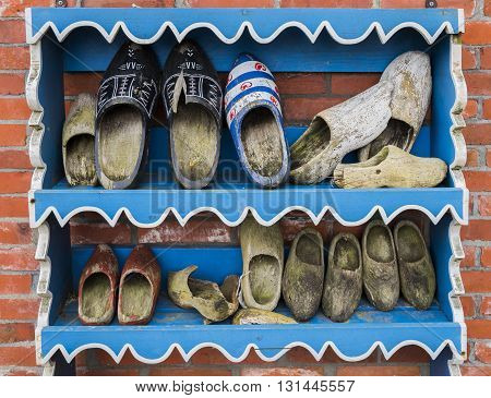 Wierum The Netherlands - April 18 2016: Several old wooden shoes on a blue painted wooden rack against a brick wall in Friesland The Netherlands.