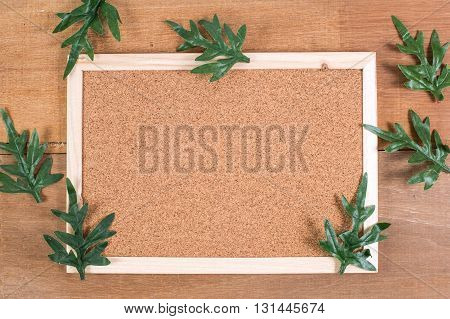 The cork board on the plank wood with the fake leaf