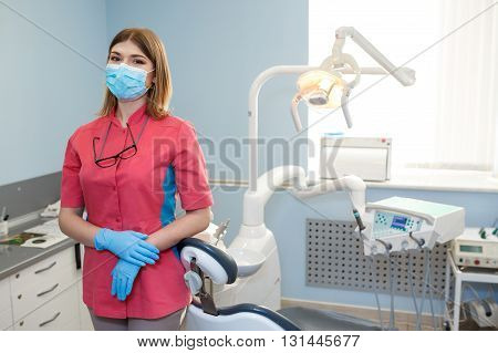 Girl Dentist Stands In The Middle Of Their Equipment And Looking At The Camera