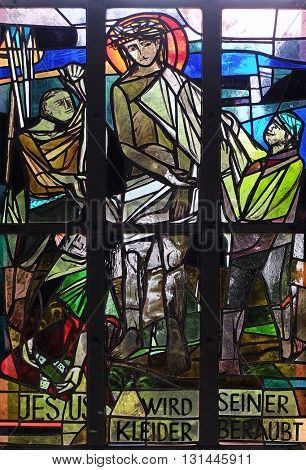 KLEINOSTHEIM, GERMANY - JUNE 08: 10th Stations of the Cross, Jesus is stripped of His garments, stained glass window in Saint Lawrence church in Kleinostheim, Germany on June 08, 2015.