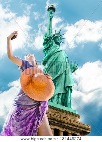 A smiling and fashionable woman with a orange wide-brimmed hat takes a selfie. Statue of Liberty and blue sky in the background. Liberty Island, New York City, United States