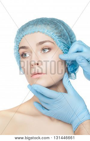 Plastic surgery concept. Doctor hands in gloves touching the beautiful woman face on white