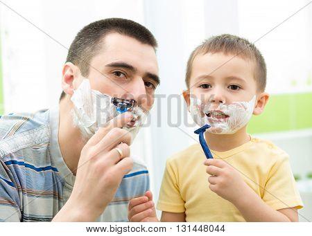 Father shaving in the mirror. Kid son imitates dad in bathroom