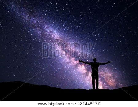 Night colorful landscape with Milky Way and silhouette of a standing sporty man with raised up arms on the mountain. Beautiful Universe. Travel background with purple sky full of stars