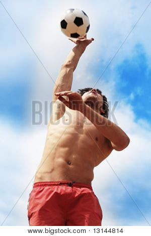 Portrait of a young man playing volleyball on a beach.