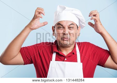 Shocked indian Chef Standing with hands spread in frustration with sad expressions on face - Isolated over blue background, frustrated asian male chef