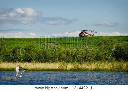 red resque helicopter on green grass with blue sky background