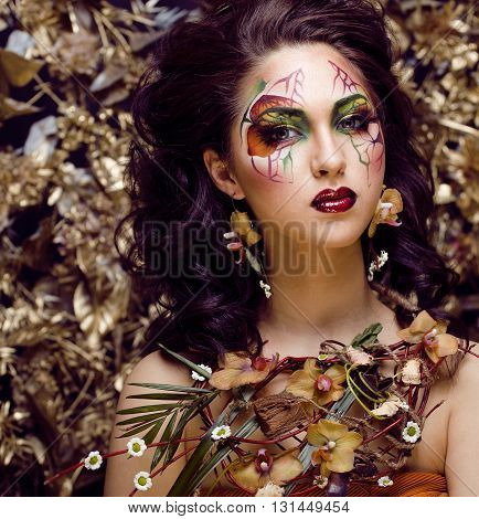 beauty woman with face art and jewelry from flowers orchids close up, creative pattern makeup floral pattern background