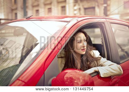 Girl driving a red car