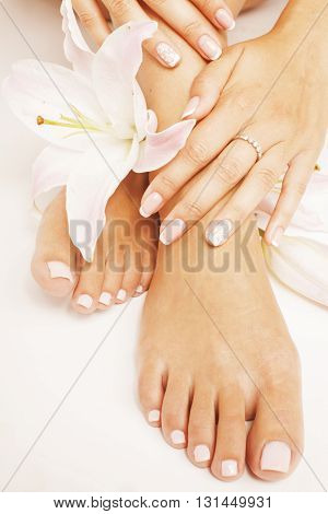 womans manicure pedicure with flower lily close up isolated on white perfect shape hands spa salon