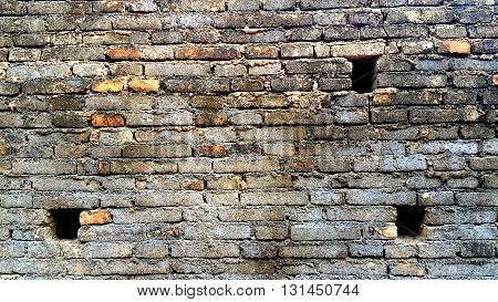 Old and dirty brick wall with three small holes