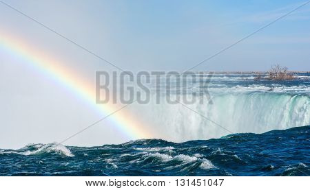 Water rushing and falling over a ledge form a mist that generates a rainbow.