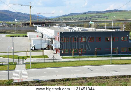 Dolny Hricov Slovakia - April 13 2016: Logistics center of international parcel delivery company DPD freight is uncharged from van. Tower cranes in background