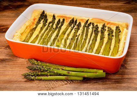 Tart with green asparagus on wooden table.